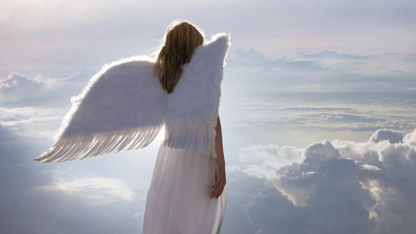 angel or archangel with wings watching from clouds