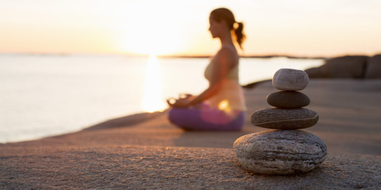 woman practices meditation on beach