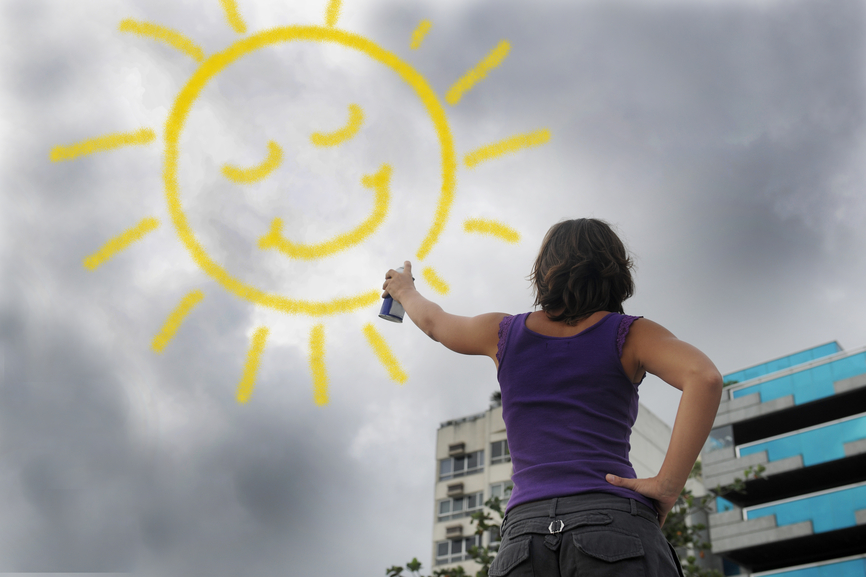 woman draw sunshine in sky focused on positive thinking